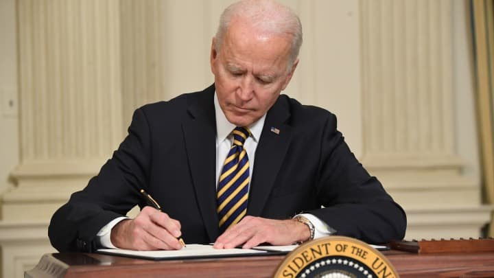 US President Joe Biden signs an executive order on securing critical supply chains, in the State Dining Room of the White House in Washington, DC, February 24, 2021.